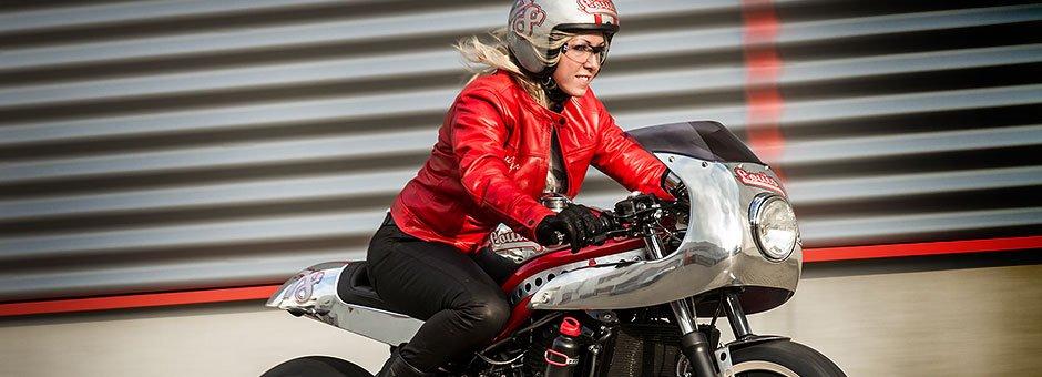Frau in Roter Biker Jacke auf einem Retro Motorrad