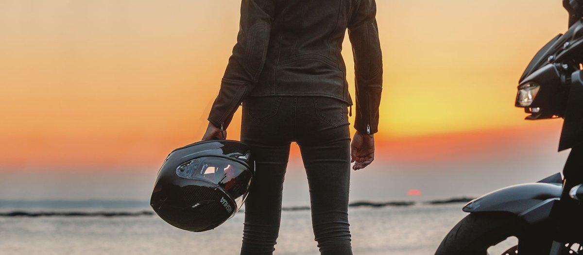 Motorrad Bikerin mit Helm vor Sonnenuntergang