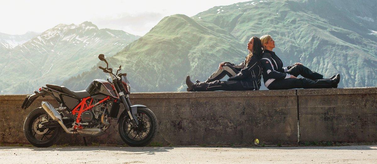 Zwei Biker Frauen sitzen neben ihren Motorrädern