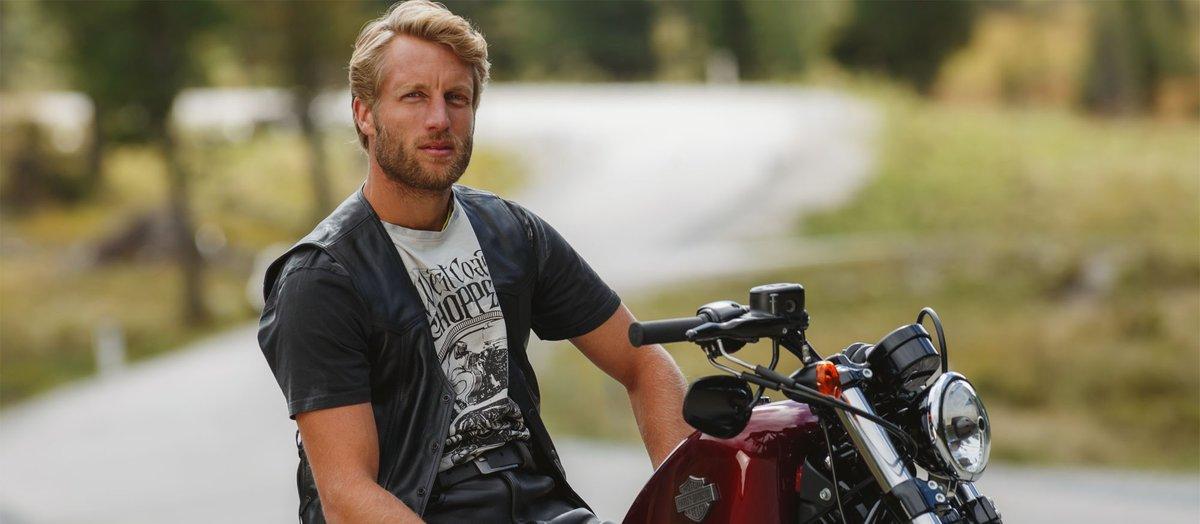 Biker sitzt in seiner Motorrad Lederweste auf seinem Chopper