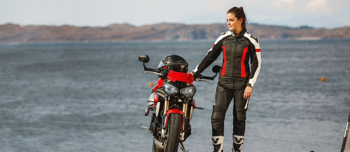 Biker Frau am Strand neben Motorrad