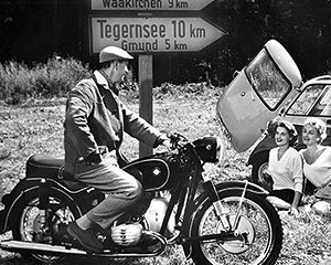 Motorcycle versus car: At the ends of the 50s compact cars became affordable vehicles for the masses.